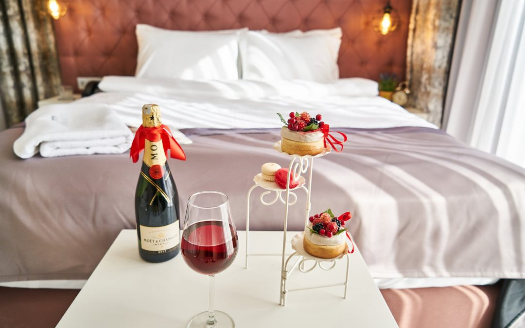 Bedroom with a bottle of wine and cupcakes on a stand
