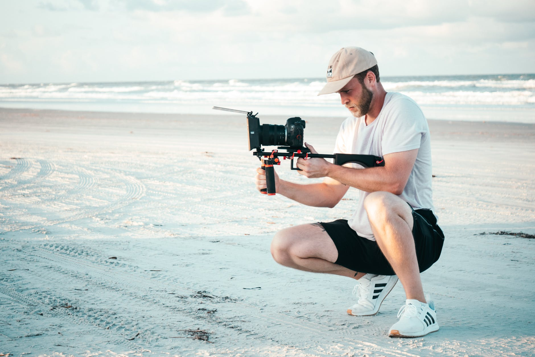 Male taking a video on the beach front