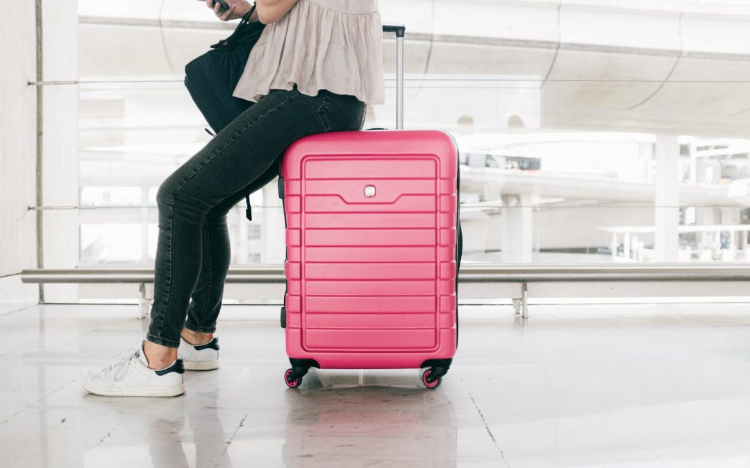Female waiting at the airport checking her phone and sitting on a pink suitcase