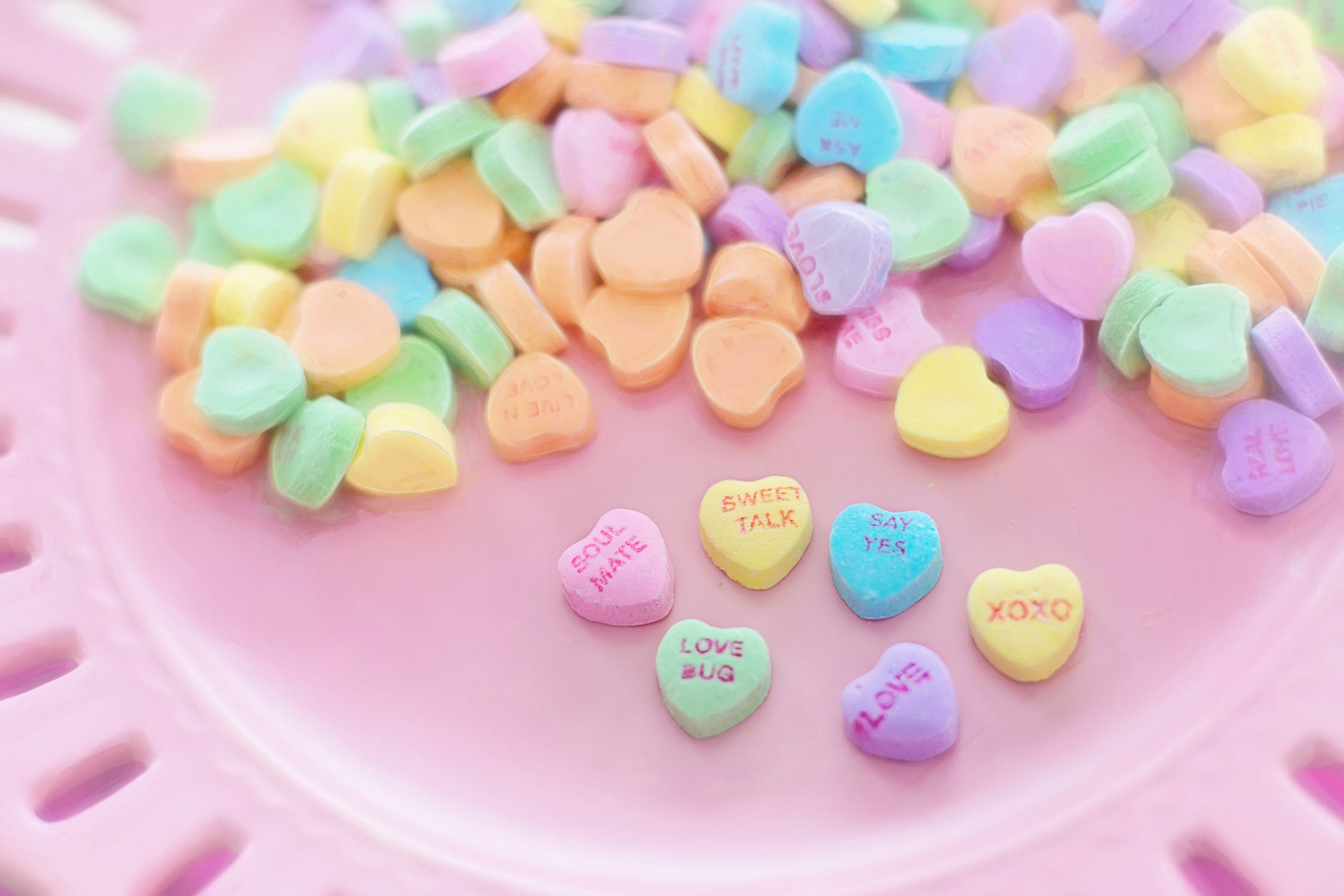 Colorful heart shaped sweets with love quotes on them