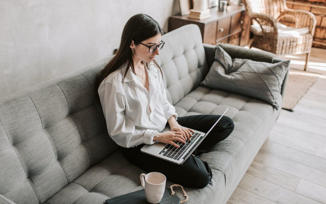 Female sitting on the couch typing on her laptop