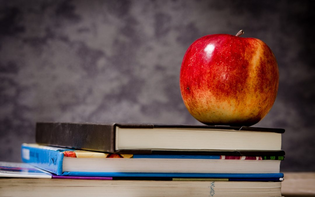 A stack of books with a red apple on top