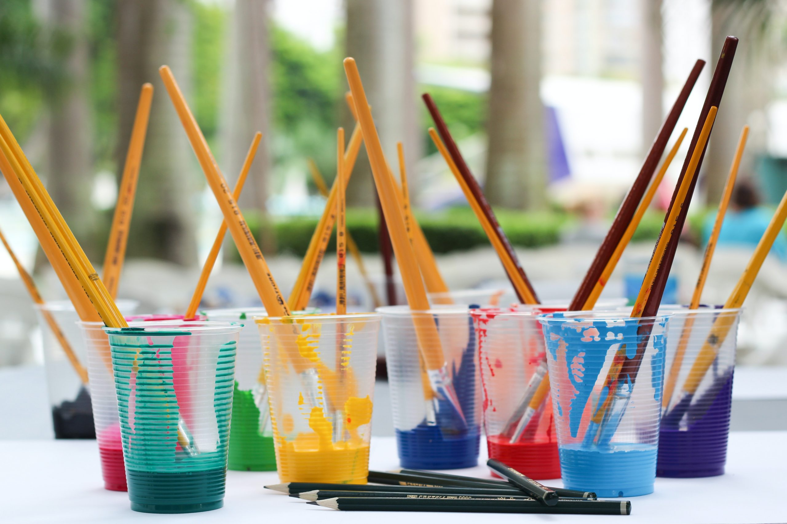 Cups with different color paint and paint brushes in them