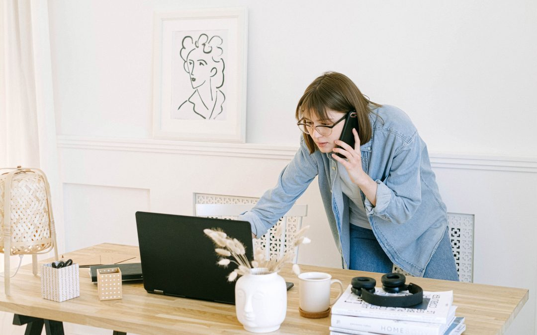 Female on the phone while checking work on her laptop