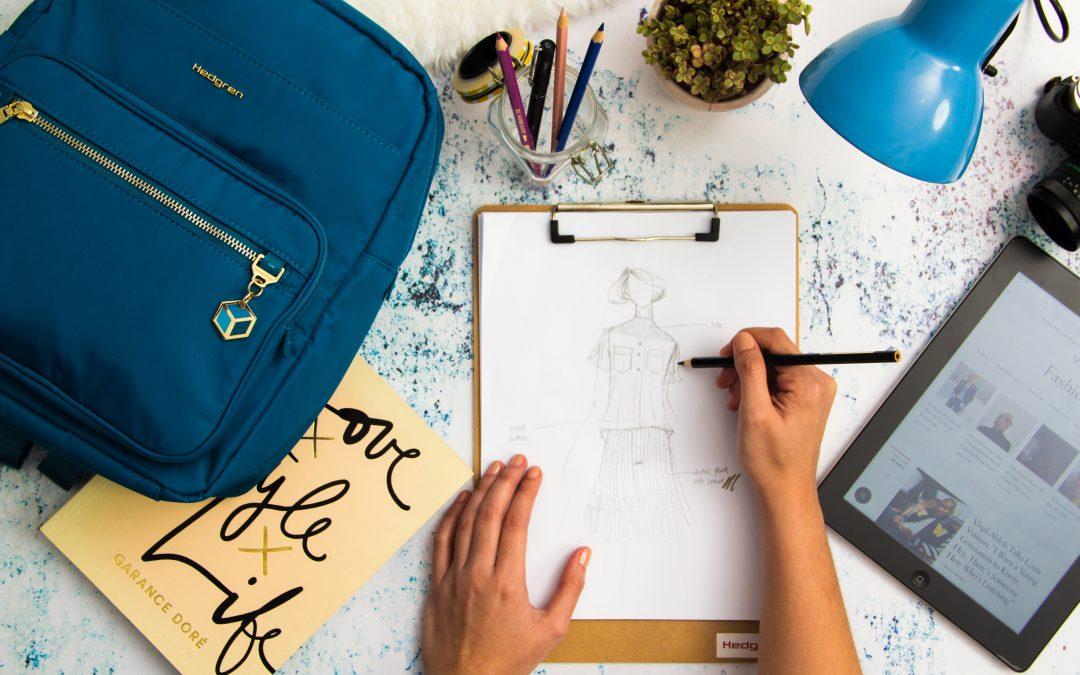 Male drawing designer clothing on paper with clipboard