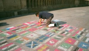 Male drawing different flags on the ground