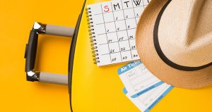 Calendar on a yellow table with flight tickets