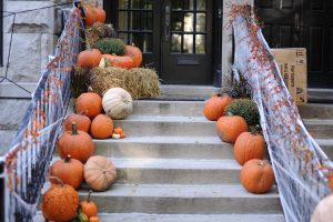 Front entrance to a house with decorated Halloween pumpkins along the steps